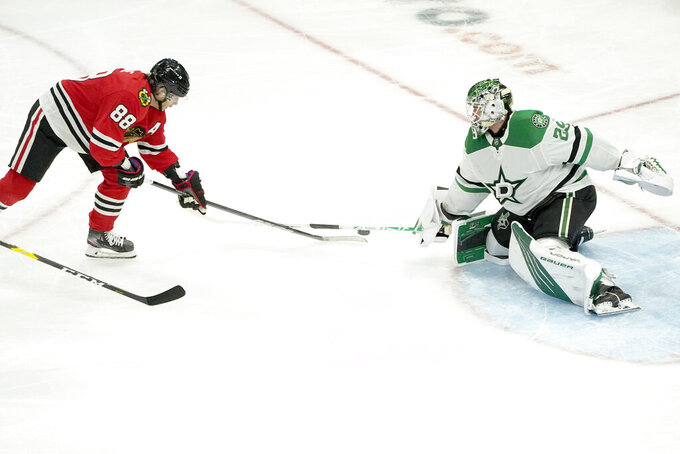 Dallas Stars goaltender Jake Oettinger, right, keeps Chicago Blackhawks' Patrick Kane from getting a shot off during the second period of an NHL hockey game Monday, May 10, 2021, in Chicago. (AP Photo/Charles Rex Arbogast)