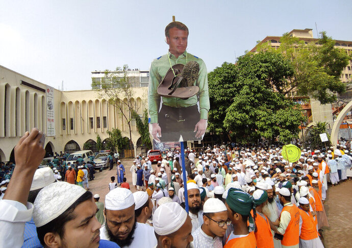 Supporters of Islami Andolan Bangladesh, an Islamist political party, carry a cutout of French President Emmanuel Macron with a garland of footwear around it as they protest against the publishing of caricatures of the Prophet Muhammad they deem blasphemous, in Dhaka, Bangladesh, Tuesday, Oct. 27, 2020. Muslims in the Middle East and beyond on Monday called for boycotts of French products and for protests over the caricatures, but Macron has vowed his country will not back down from its secular ideals and defense of free speech. (AP Photo/Mahmud Hossain Opu)