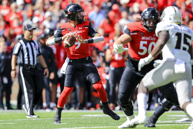 Cincinnati quarterback Desmond Ridder (9) throws a pass for a touchdown during the first half of an NCAA college football game against UCF, Saturday, Oct. 16, 2021, in Cincinnati. (AP Photo/Aaron Doster)