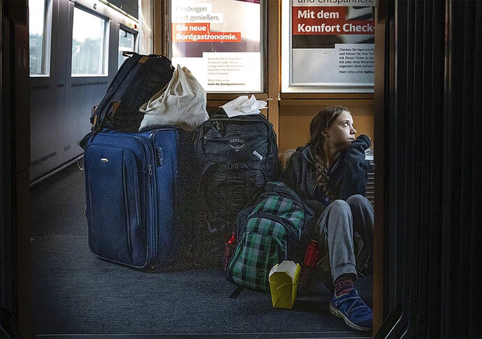 """In this image taken from Twitter feed of Climate activist Greta Thunberg, showing Thunberg sitting on the floor of a train surrounded by bags Saturday Dec. 14, 2019, with the comment """"traveling on overcrowded trains through Germany. And I'm finally on my way home!""""  The Tweet created a tweetstorm online Sunday about the performance of German railways, but the 16-year-old Swedish activist later sought to draw a line under the matter by tweeting that she eventually got a seat and that overcrowded trains are a good thing showing public transport is popular. (Twitter @GretaThunberg via AP)"""