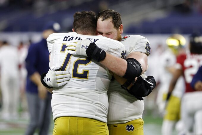 Notre Dame offensive lineman Robert Hainsey (72) and offensive lineman Tommy Kraemer, right, greet each other on the field after their 31-14 loss to Alabama in the Rose Bowl NCAA college football game in Arlington, Texas, Friday, Jan. 1, 2021. (AP Photo/Michael Ainsworth)