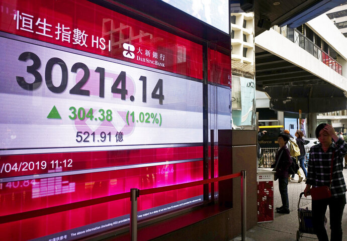 People walk past an electronic board showing Hong Kong share index outside a local bank in Hong Kong, Monday, April 15, 2019. Asian markets were broadly higher Monday on signs that the U.S. and China were closing in on a trade deal after months of negotiations. (AP Photo/Vincent Yu)
