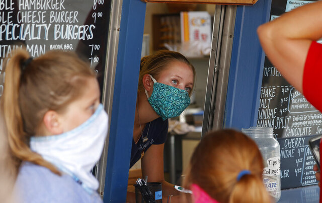 FILE - In this Aug. 4, 2020 file photo, a staffer wears a mask while taking orders at a small restaurant in Grand Lake, Colo., amid the coronavirus pandemic.  The coronavirus pandemic has put millions of Americans out of work. But many of those still working are fearful, distressed and stretched thin, according to a new poll by The Associated Press-NORC Center for Public Affairs Research.  (AP Photo/David Zalubowski, File)