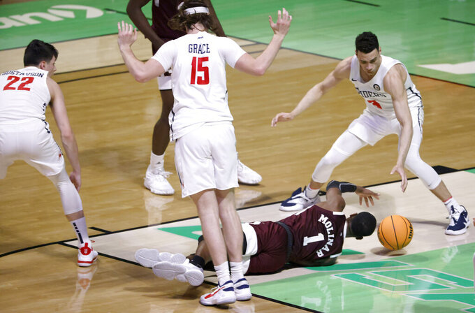 Mississippi State guard Iverson Molinar (1) goes to floor for a loose ball as Richmond guard Andre Gustavson (22) and Richmond forwards Matt Grace (15) and Tyler Burton (3) watch during the first half of an NCAA college basketball game in the semifinals of the NIT, Thursday, March 25, 2021, in Denton, Texas. (AP Photo/Ron Jenkins)
