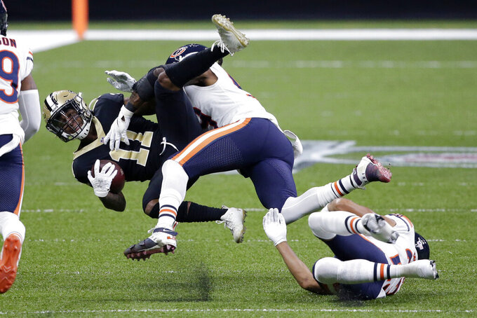 New Orleans Saints wide receiver Deonte Harris (11) is tackled by Chicago Bears inside linebacker Danny Trevathan and cornerback Kyle Fuller, right, in the first half of an NFL wild-card playoff football game in New Orleans, Sunday, Jan. 10, 2021. (AP Photo/Butch Dill)