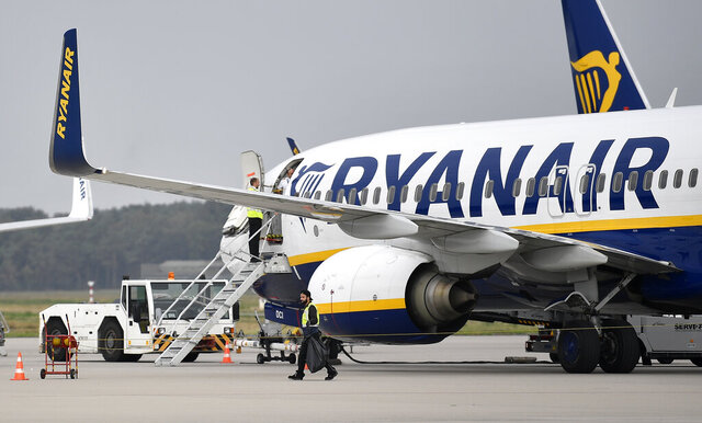 FILE - In this Sept. 12, 2018 file photo, a Ryanair plane parks at the airport in Weeze, Germany. Boeing's troubled 737 Max jet is getting a vote of confidence from Ireland's Ryanair, one of Europe's biggest budget airlines.  Ryanair announced Thursday, Dec. 3, 2020, that it will order 75 more Max jets, bringing its total orders to 210. The move comes just weeks before the plane is expected to resume flying. (AP Photo/Martin Meissner, File)