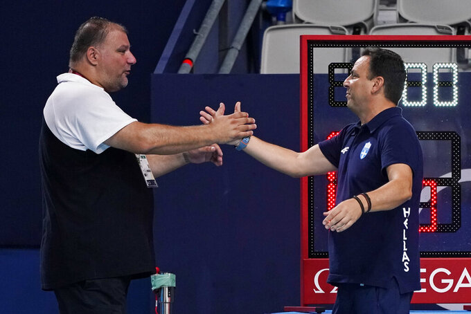 Serbia's head coach Dejan Savic, left, shakes hands with Greece's head coach Theodoros Vlachos after Serbia won the men's water polo gold medal match at the 2020 Summer Olympics, Sunday, Aug. 8, 2021, in Tokyo, Japan. (AP Photo/Mark Humphrey)