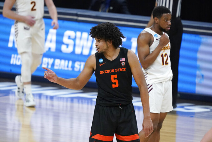 Oregon State guard Ethan Thompson (5) celebrates in front of Loyola Chicago guard Marquise Kennedy (12) at the end of a Sweet 16 game in the NCAA men's college basketball tournament at Bankers Life Fieldhouse, Saturday, March 27, 2021, in Indianapolis. Oregon State won 65-58. (AP Photo/Jeff Roberson)