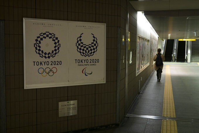 A commuter leaves a train station adorned with posters promoting the Tokyo 2020 Olympics in Tokyo, Monday, March 23, 2020. The IOC will take up to four weeks to consider postponing the Tokyo Olympics amid mounting criticism of its handling of the coronavirus crisis that now includes a call for delay from the leader of track and field, the biggest sport at the games. (AP Photo/Jae C. Hong)