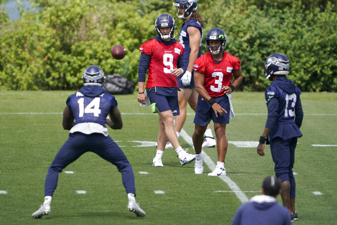 Seattle Seahawks quarterback Russell Wilson (3) passes to wide receiver DK Metcalf (14) during NFL football practice Tuesday, June 8, 2021, in Renton, Wash., as quarterback Danny Etling (9) and wide receiver Darvin Kidsy (23) look on. (AP Photo/Ted S. Warren)