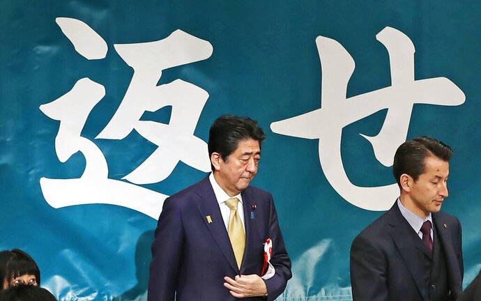 """Japanese Prime Minister Shinzo Abe, second from right, arrives to deliver a speech during an annual rally, calling on Russia to return disputed islands which Japan calls the Northern Territories and Russia calls Kuril Islands, in Tokyo Thursday, Feb. 7, 2019. Abe vowed to take a """"step-by-step"""" approach in resolving a territorial dispute with Russia left over from World War II. Abe said that settling the conflict over islands north of Hokkaido that are controlled by Russia was difficult but necessary. Japanese slogans partially seen in the background read:"""