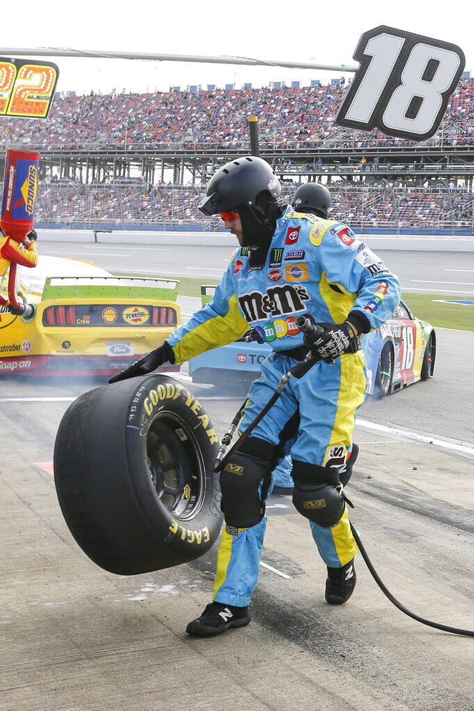 A crew member for Kyle Busch (18) bounces a tire as he runs back to the wall during a NASCAR Cup Series auto race at Talladega Superspeedway, Monday, Oct 14, 2019, in Talladega, Ala. (AP Photo/Butch Dill)