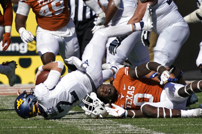 Texas' DeMarvion Overshown (0) loses his helmet as he sacks West Virginia quarterback Jarret Doege (2) during the second half of an NCAA college football game in Austin, Texas, Saturday, Nov. 7, 2020. (AP Photo/Chuck Burton)