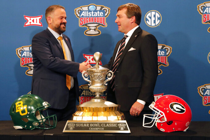Georgia head coach Kirby Smart, right, and Baylor head coach Matt Rhule shake hands as they pose with the trophy during a Sugar Bowl NCAA college news conference in New Orleans, Tuesday, Dec. 31, 2019. The two teams meet on New Year's Day. (AP Photo/Gerald Herbert)