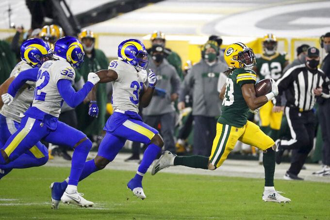 Green Bay Packers' Aaron Jones, right, is chased by the Los Angeles Rams during the second half of an NFL divisional playoff football game Saturday, Jan. 16, 2021, in Green Bay, Wis. (AP Photo/Mike Roemer)
