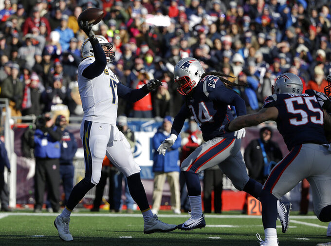 Los Angeles Chargers quarterback Philip Rivers, left, passes under pressure from New England Patriots linebacker Dont'a Hightower (54) during the first half of an NFL divisional playoff football game, Sunday, Jan. 13, 2019, in Foxborough, Mass. (AP Photo/Steven Senne)