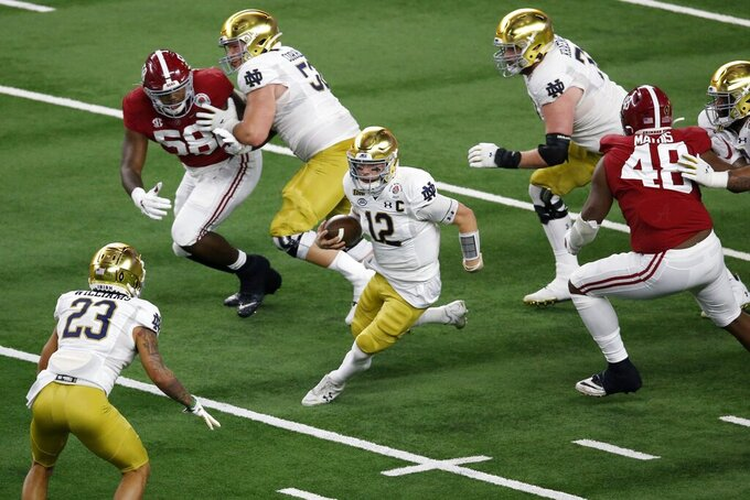 Notre Dame quarterback Ian Book (12) runs the ball as Alabama defensive lineman Christian Barmore (58) and defensive lineman Phidarian Mathis (48) give chase in the first half of the Rose Bowl NCAA college football game in Arlington, Texas, Friday, Jan. 1, 2021. (AP Photo/Roger Steinman)