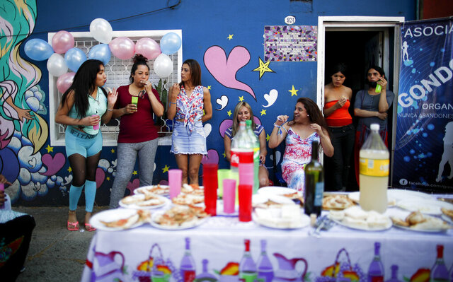 Transgender women celebrate Pride Day at the Hotel Gondolin where they live in Buenos Aires, Argentina, Saturday, Nov. 7, 2020. In September, President Alberto Fernández signed a decree establishing a 1% employment quota for transgender people in the public sector.  (AP Photo/Natacha Pisarenko)