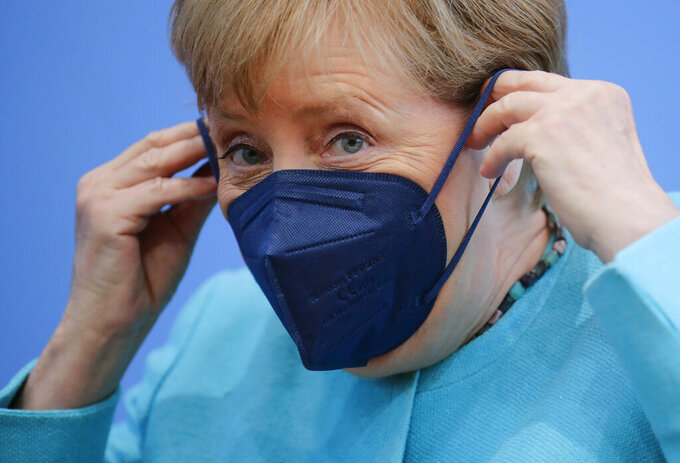 German Chancellor Angela Merkel  puts on her face mask as she leaves, after her annual summer news conference in Berlin, Germany, Thursday, July 22, 2021. (Hannibal Hanschke/Pool Photo via AP)
