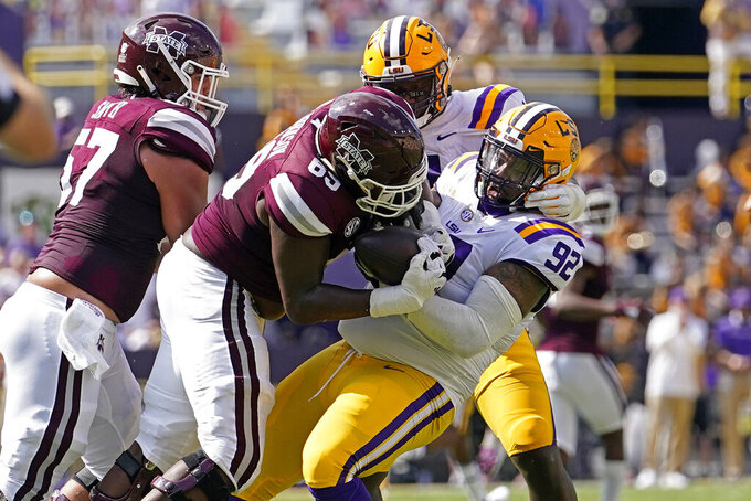 LSU defensive end Neil Farrell Jr. (92) tries to intercept a pass that was batted into the air as Mississippi State offensive lineman JT Zakkak (65) comes down with the completion in the first half an NCAA college football game in Baton Rouge, La., Saturday, Sept. 26, 2020. (AP Photo/Gerald Herbert)