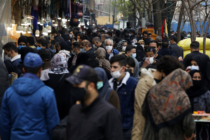 "Mask-clad shoppers walk at Tehran's Grand Bazaar, ahead of the Persian New Year, or Nowruz, meaning ""New Day."" Iran, Monday, March 15, 2021. (AP Photo/Vahid Salemi)"