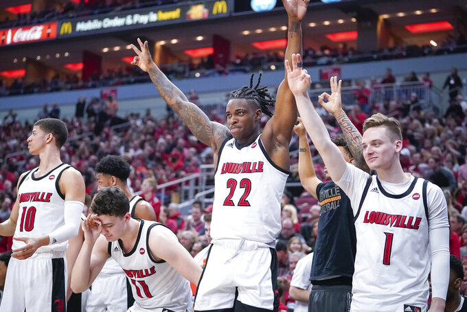 The Louisville bench celebrates after a score during the first half of an NCAA college basketball game against Virginia, Saturday, Feb 8, 2020 in Louisville, Ky. (AP Photo/Bryan Woolston)