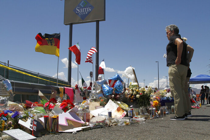 FILE - In this Aug. 12, 2019 photo, mourners visit the makeshift memorial near the Walmart in El Paso, Texas, where 22 people were killed in a mass shooting that police are investigating as a terrorist attack targeting Latinos. State officials are testifying, Wednesday, Oct. 30, 2019, before the Senate Select Committee on Mass Violence Prevention and Community Safety, that's evaluating issues related to mass violence. (AP Photo/Cedar Attanasio, File)