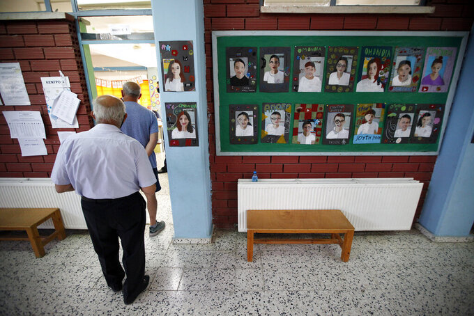 Voters wait in a line to casts their vote at a polling station during the parliamentary elections in Deftera, a suburb of capital Nicosia, Cyprus, Sunday, May 30, 2021. Cypriots are voting for a new parliament, with some 558,000 voters eligible to elect 56 lawmakers. (AP Photo/Petros Karadjias)