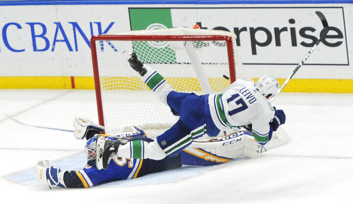 Vancouver Canucks' Josh Leivo (17) trips over St. Louis Blues' Jordan Binnington (50) as he scores the winning goal during a shootout in an NHL hockey game, Thursday, Oct. 17, 2019, in St. Louis. (AP Photo/Bill Boyce)