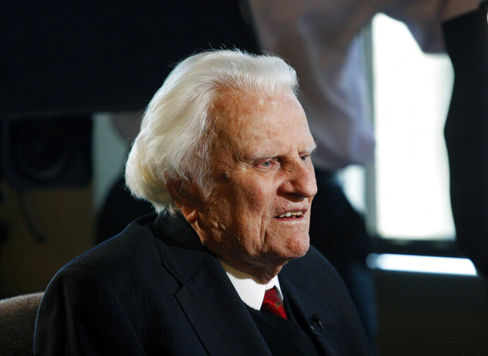 FILE - In this Dec. 20, 2010 file photo, Evangelist Billy Graham is interviewed at the Billy Graham Evangelistic Association headquarters in Charlotte, N.C. The Billy Graham Library in North Carolina says it has seen a surge in visitors in the year since its namesake's death. Citing a blog post on the library's website, WLOS-TV reports that 214,000 people visited the Charlotte complex in 2018, up from 144,000 in 2017. According to the post, visitors came from 55 countries. Graham died Feb. 21, 2018, at age 99. (AP Photo/Nell Redmond, File)