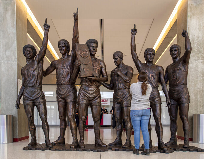 A statue of the in the lobby of Assembly Hall, home to the Indiana Hoosiers, greets guests as they arrive for a first round game in the NCAA men's college basketball tournament, Saturday, March 20, 2021, in Bloomington, Ind. The statue depicts players of the 1975-76 Hoosier team that remains the last to finish a perfect season (32-0). The players, from left to right, are: Bobby Wilkerson, Ken Benson, Scott May, Quinn Buckner, Jim Crews, and Tom Abernethy. (AP Photo/Doug McSchooler)