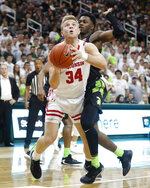 Wisconsin guard Brad Davison (34), defended by Michigan State guard Rocket Watts, attempts a layup during the first half of an NCAA college basketball game, Friday, Jan. 17, 2020, in East Lansing, Mich. (AP Photo/Carlos Osorio)