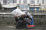Laborers cover themselves with a plastic sheet in the rain as they wait for customers in Kabul, Afghanistan, Monday, April 6, 2020. (AP Photo/Rahmat Gul)