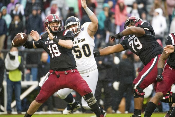 South Carolina quarterback Jake Bentley (19) throws a pass under pressure from Akron defensive lineman Brock Boxen (50) during the first half of an NCAA college football game Saturday, Dec. 1, 2018, in Columbia, S.C. South Carolina defeated Akron 28-3. (AP Photo/Sean Rayford)
