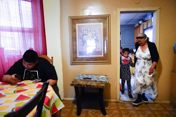 """Amanda Brebe, 75, walks with her granddaughter Zuniga Gonzales, 7, as Erick Zuniga Gonzales, 17, sits at the dining room table the Kensington section of Philadelphia, Sunday, May 16, 2021. The family is trying to rebuild their lives together after they were separated under a former """"zero-tolerance"""" policy to criminally prosecute adults who entered the country illegally. (AP Photo/Matt Rourke)"""
