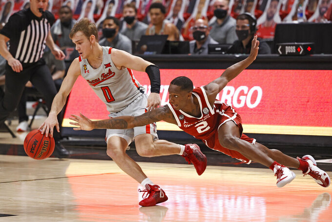 Oklahoma's Umoja Gibson (2) tries to steal the ball from Texas Tech's Mac McClung (0) during the second half of an NCAA college basketball game Monday, Feb. 1, 2021, in Lubbock, Texas. (AP Photo/Brad Tollefson)