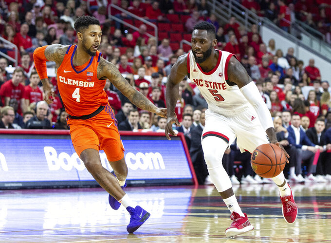 North Carolina State's Eric Lockett (5) drives against Clemson's Shelton Mitchell (4) during the first half of an NCAA college basketball game in Raleigh, N.C., Saturday, Jan. 26, 2019. (AP Photo/Ben McKeown)