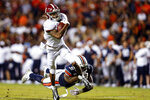 FILE - Alabama wide receiver DeVonta Smith (6) catches a pass as Auburn linebacker Chandler Wooten (31) tries to tackle him during the second half of an NCAA college football game in Auburn, Ala. , in this Saturday, Nov. 30, 2019, file photo. The Southeastern Conference championship game features two of the nation's top playmakers, and neither is a quarterback. Alabama receiver DeVonta Smith and Florida tight end Kyle Pitts are the real stars of the league's most potent offenses. (AP Photo/Butch Dill, File)