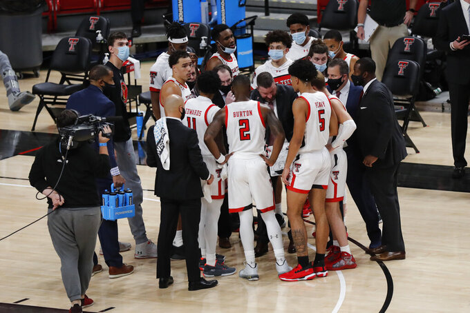 Texas Tech coach Chris Beard meets with his team during a timeout in the first half of the team's NCAA college basketball game against Northwestern State, Wednesday Nov. 25, 2020, in Lubbock, Texas. (AP Photo/Mark Rogers)