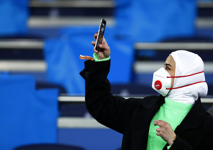 A fan wearing a protective mask takes a picture with her cell phone prior the Champions League, round of 16, first leg soccer match between Real Madrid and Manchester City at the Santiago Bernabeu stadium in Madrid, Spain, Wednesday, Feb. 26, 2020. (AP Photo/Manu Fernandez)