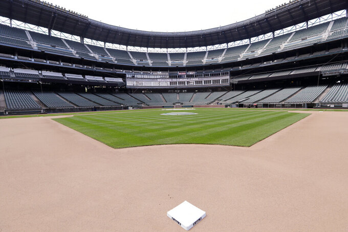 Second base sits in its place in an otherwise empty ballpark where grounds crew members continue to keep the Seattle Mariners' field in playing shape as the ballpark goes into its seventh week without baseball played because of the coronavirus outbreak Monday, May 11, 2020, in Seattle. A person familiar with the decision tells The Associated Press that Major League Baseball owners have given the go-ahead to making a proposal to the players' union that could lead to the coronavirus-delayed season starting around the Fourth of July weekend in ballparks without fans. (AP Photo/Elaine Thompson)