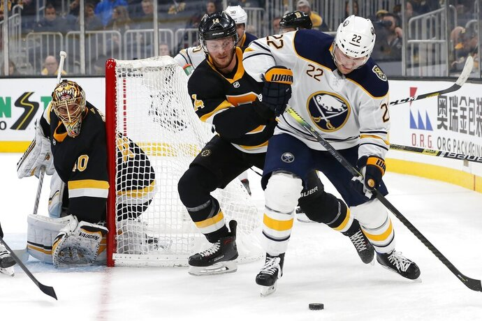 Boston Bruins' Chris Wagner (14) battles Buffalo Sabres' Johan Larsson (22) for the puck during the second period of an NHL hockey game in Boston, Sunday, Dec. 29, 2019. (AP Photo/Michael Dwyer)