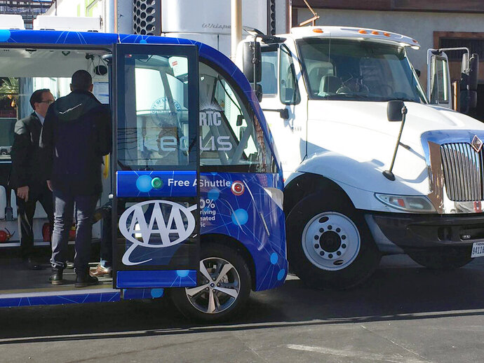 FILE - This Nov. 8, 2017, file photo by KVVU reporter Kathleen Jacob shows a driverless shuttle bus after it collided with a big rig in Las Vegas. Federal investigators say a collision between an experimental self-driving shuttle and a semi in downtown Las Vegas was probably the truck driver's fault. But the shuttle operator didn't have quick access to a controller that could have honked the horn or moved the shuttle, contributing to the accident. (Kathleen Jacob/KVVU-TV via AP, File)