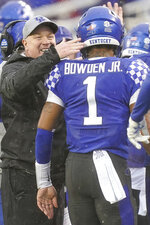 Kentucky coach Mark Stoops congratulates quarterback Lynn Bowden Jr. (1) after he scored a touchdown during the second half of the NCAA college football game against Louisville, Saturday, Nov. 30, 2019, in Lexington, Ky. (AP Photo/Bryan Woolston)