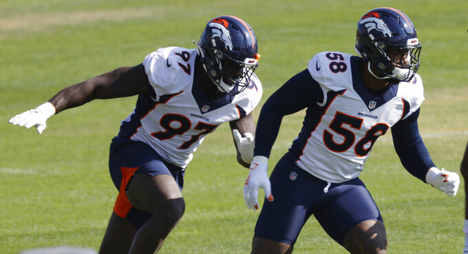 Denver Broncos linebackers Von Miller, right, and Jeremiah Attaochu take part in drills during an NFL football practice Monday, Aug. 31, 2020, in Englewood, Colo. (AP Photo/David Zalubowski)