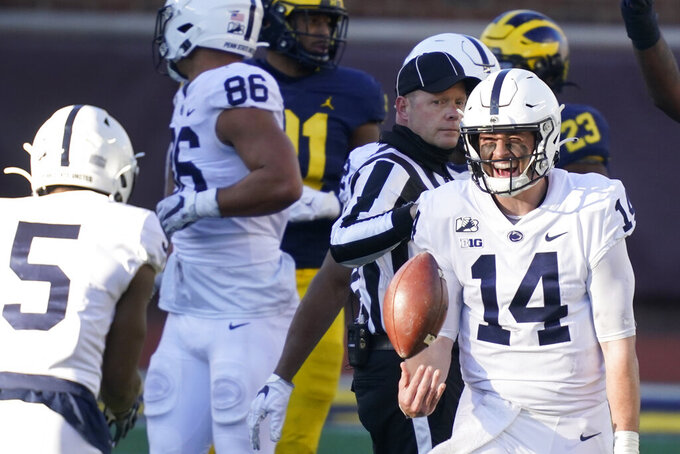 Penn State quarterback Sean Clifford (14) celebrates his team's win over Michigan with wide receiver Jahan Dotson (5) after an NCAA college football game, Saturday, Nov. 28, 2020, in Ann Arbor, Mich. (AP Photo/Carlos Osorio)