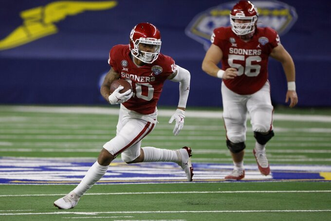 Oklahoma wide receiver Theo Wease (10) sprints to the end zone for a touchdown against Florida after catching a pass as offensive lineman Creed Humphrey (56) watches during the first half of the Cotton Bowl NCAA college football game in Arlington, Texas, Wednesday, Dec. 30, 2020. (AP Photo/Ron Jenkins)