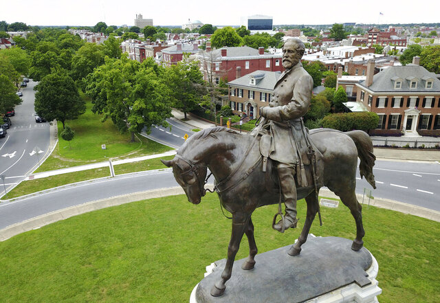 FILE - This June 27, 2017, file photo, shows the statue of Confederate General Robert E. Lee that stands in the middle of a traffic circle on Monument Avenue in Richmond, Va.  A lawsuit seeking to prevent Virginia Gov. Ralph Northam's administration from removing an enormous statue of Gen. Lee can proceed, a judge ruled Tuesday, Aug. 25, 2020, clearing the way for a trial in the fall. (AP Photo/Steve Helber, File)