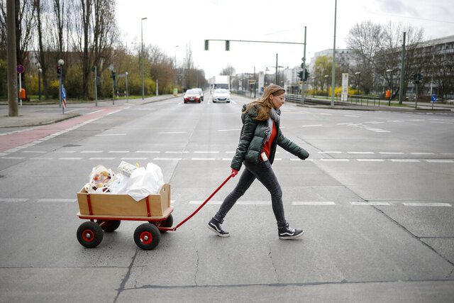 Social worker Rebekka Rauchhaus of the Christian charity the Arche, or Ark, pulls a cart as she walks through the district Hellersdorf to deliver food, toys and hygiene products to poor families in the Hellersdorf suburb of Berlin, Germany, Thursday, April 2, 2020. The group that provides help to about 1,300 poor families across Germany is now delivering to their doorstep during the coronavirus pandemic. (AP Photo/Markus Schreiber)