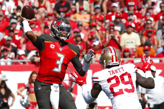 Tampa Bay Buccaneers quarterback Jameis Winston (3) works under pressure in the pocket aganst San Francisco 49ers strong safety Jaquiski Tartt (29) during the first half an NFL football game, Sunday, Sept. 8, 2019, in Tampa, Fla. (AP Photo/Mark LoMoglio)